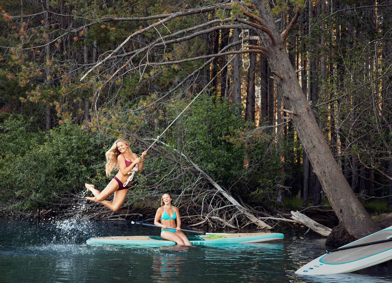 Two girls with paddle boards trying out a rope swing.