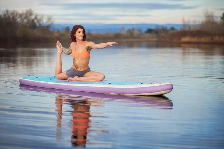 Young woman doing yoga on a stand up paddle board on a small lake in Northern California.