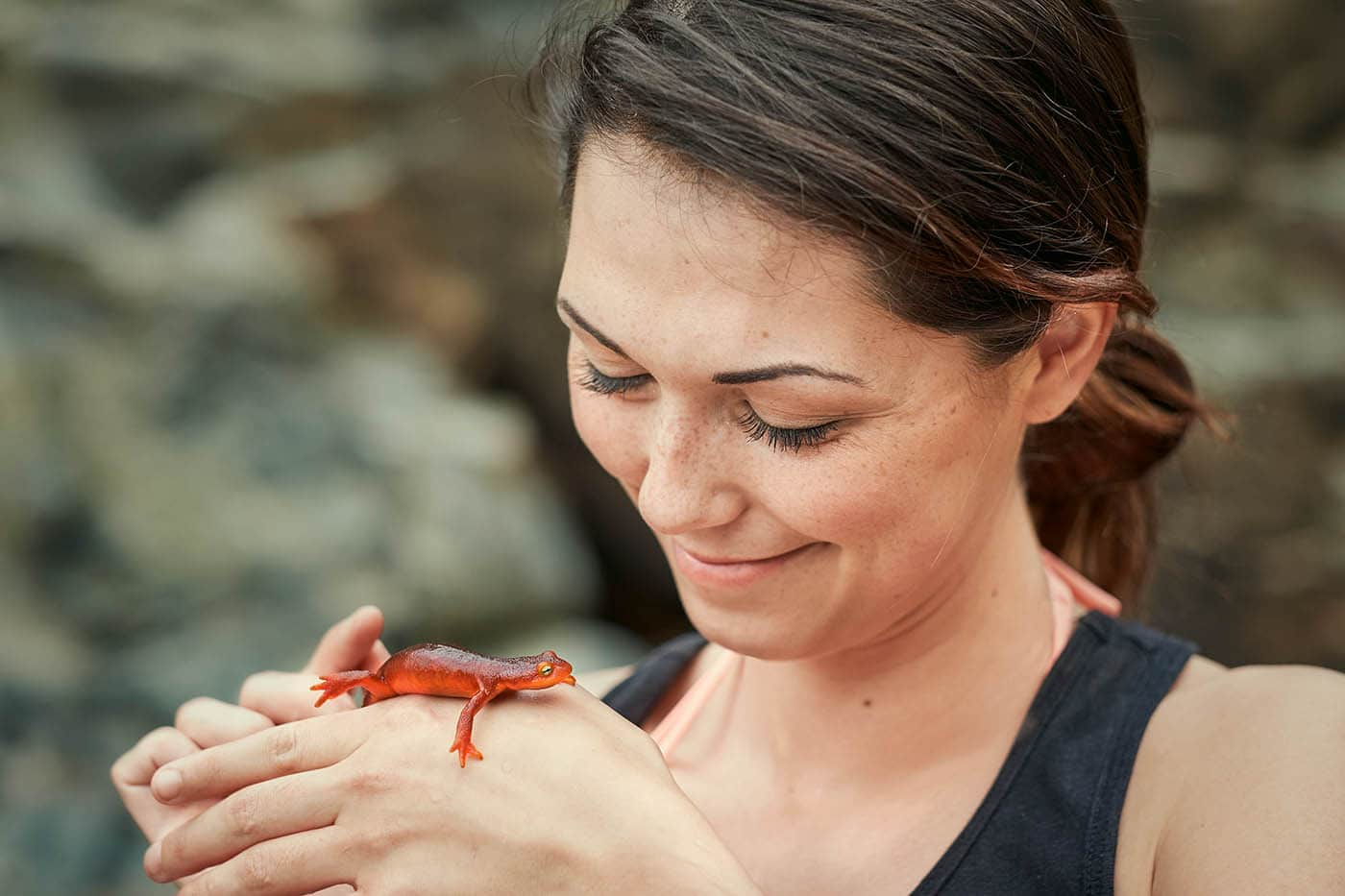 A young woman smiling while holding a Sierra Newt in Northern California.