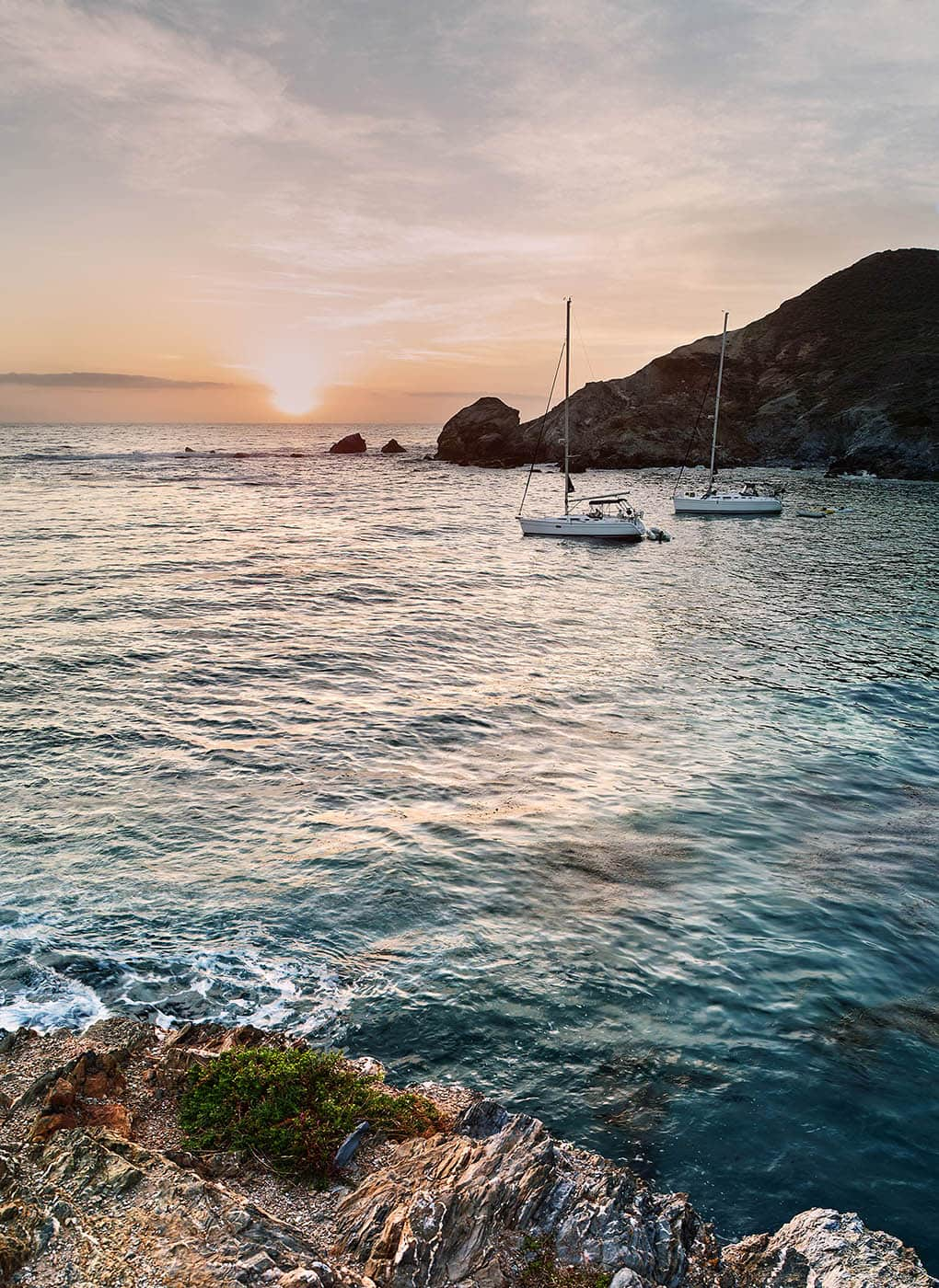 Two sailboats anchored at Little Harbor on Catalina Island at sunset.