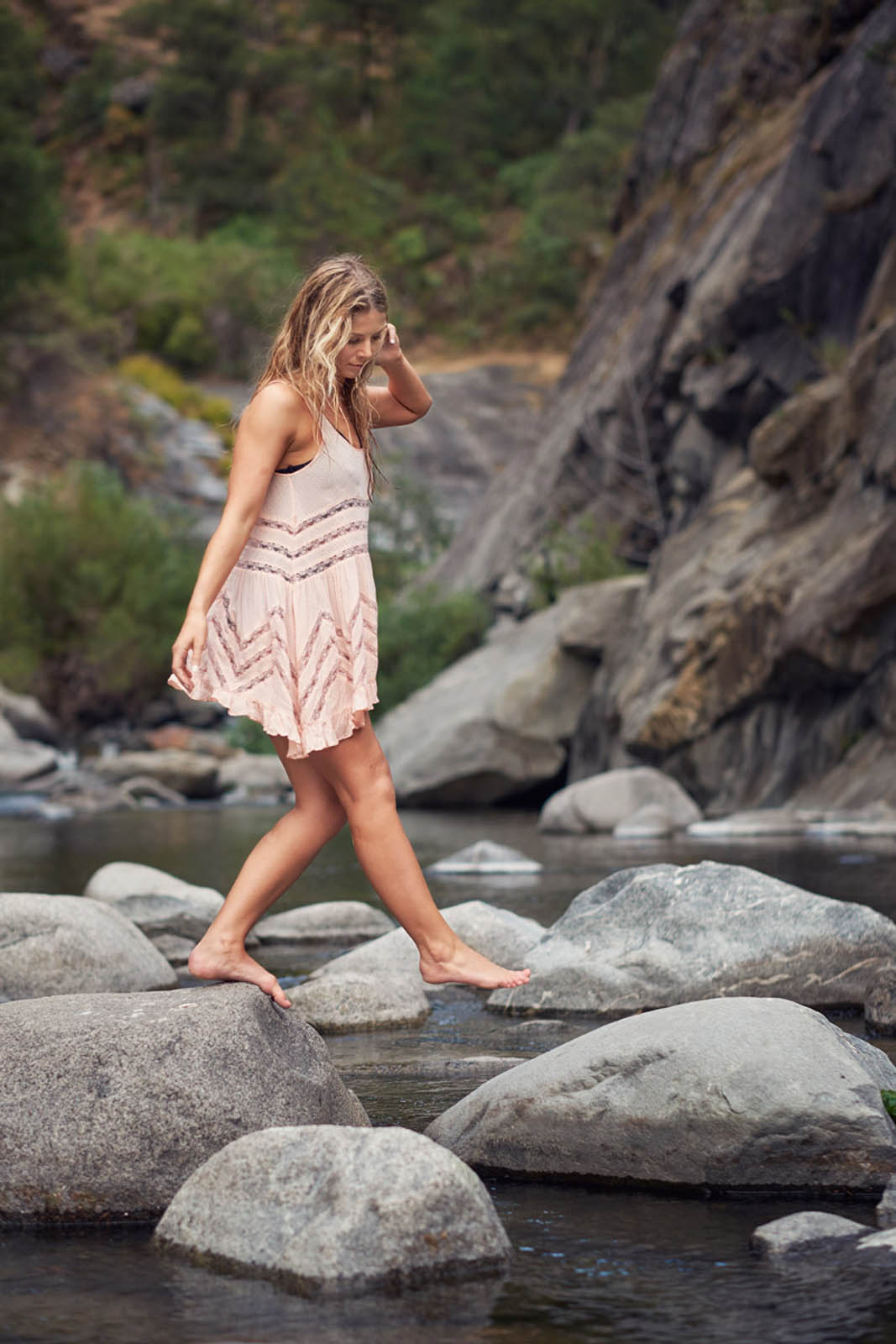 A Barefoot Woman in a Dress Walking Across a Creek.