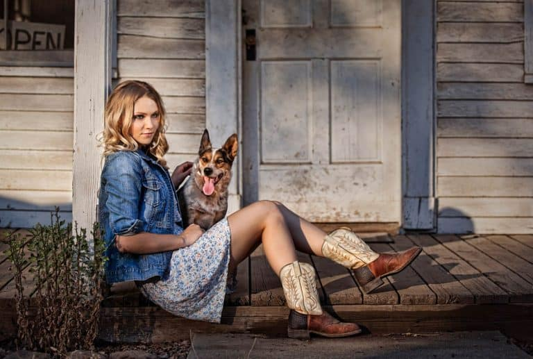 Young woman in a dress and cowboy boots on a porch with her dog on a summer evening.
