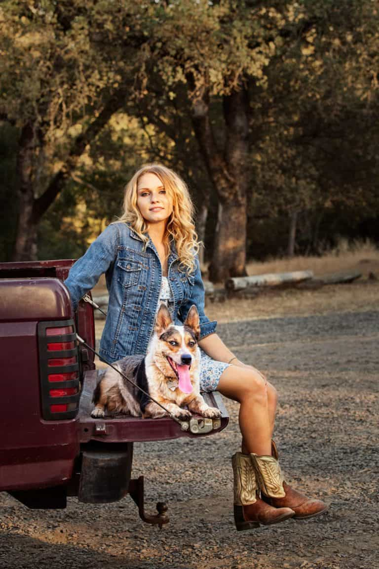 Rural lifestyle photography of country girl on a truck tail gate with her dog.