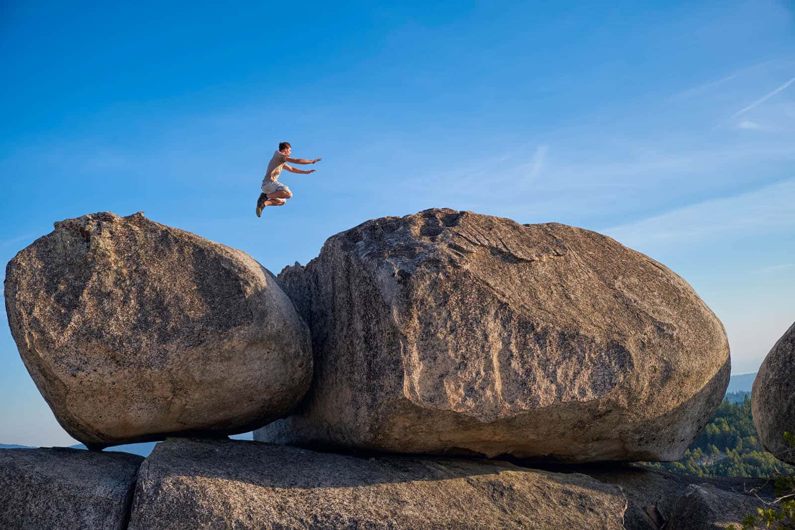 Teenage boy in a remote location in Northern California jumping from one large boulder to another one.