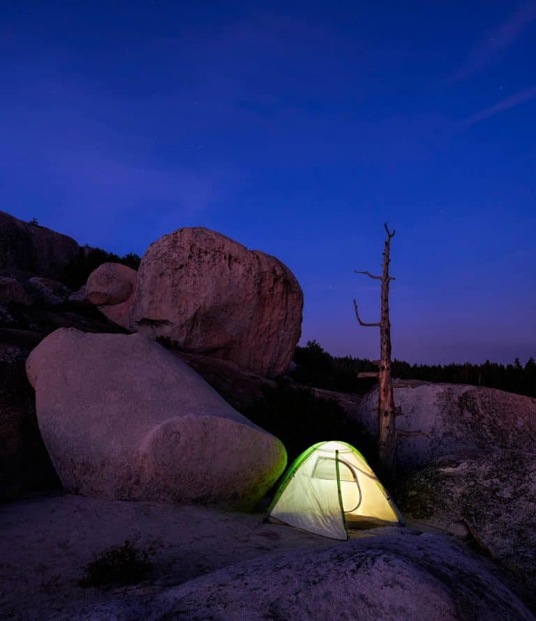 Tent on a camping trip at night on a barren, rocky landscape surrounded by granite boulders.