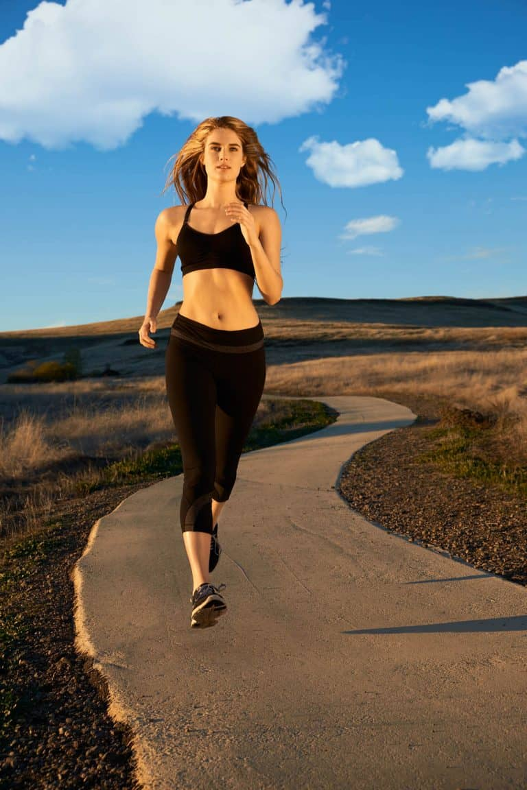 A young woman in black active wear jogging on an outdoor running trail on a Fall Afternoon.