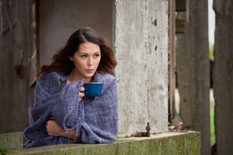 Woman on a farm drinking coffee.