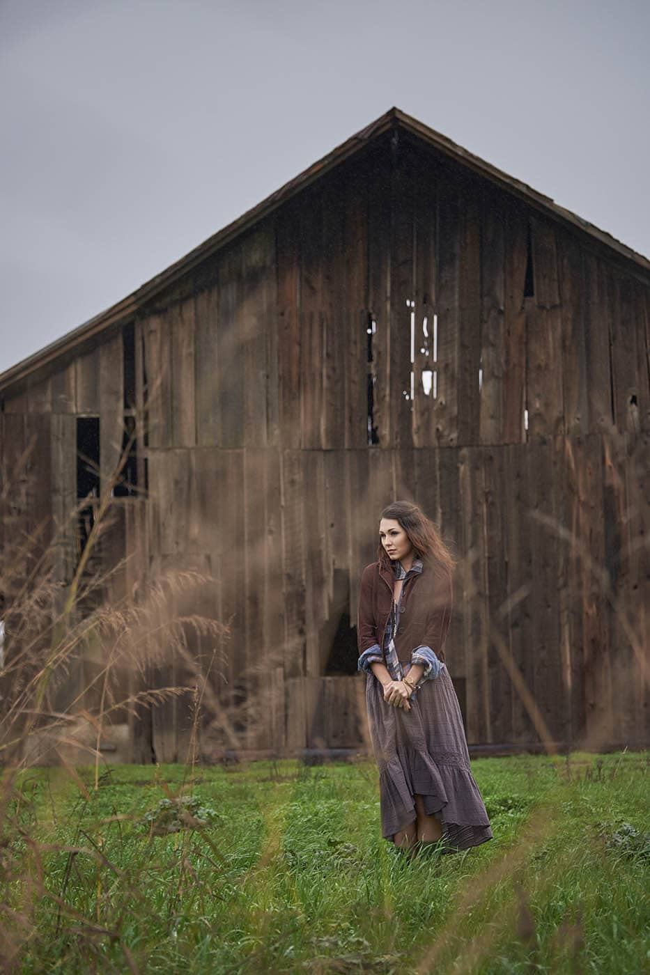 A young woman wearing a dress and rubber boots walking through a field on a small farm on a cloudy winter day.