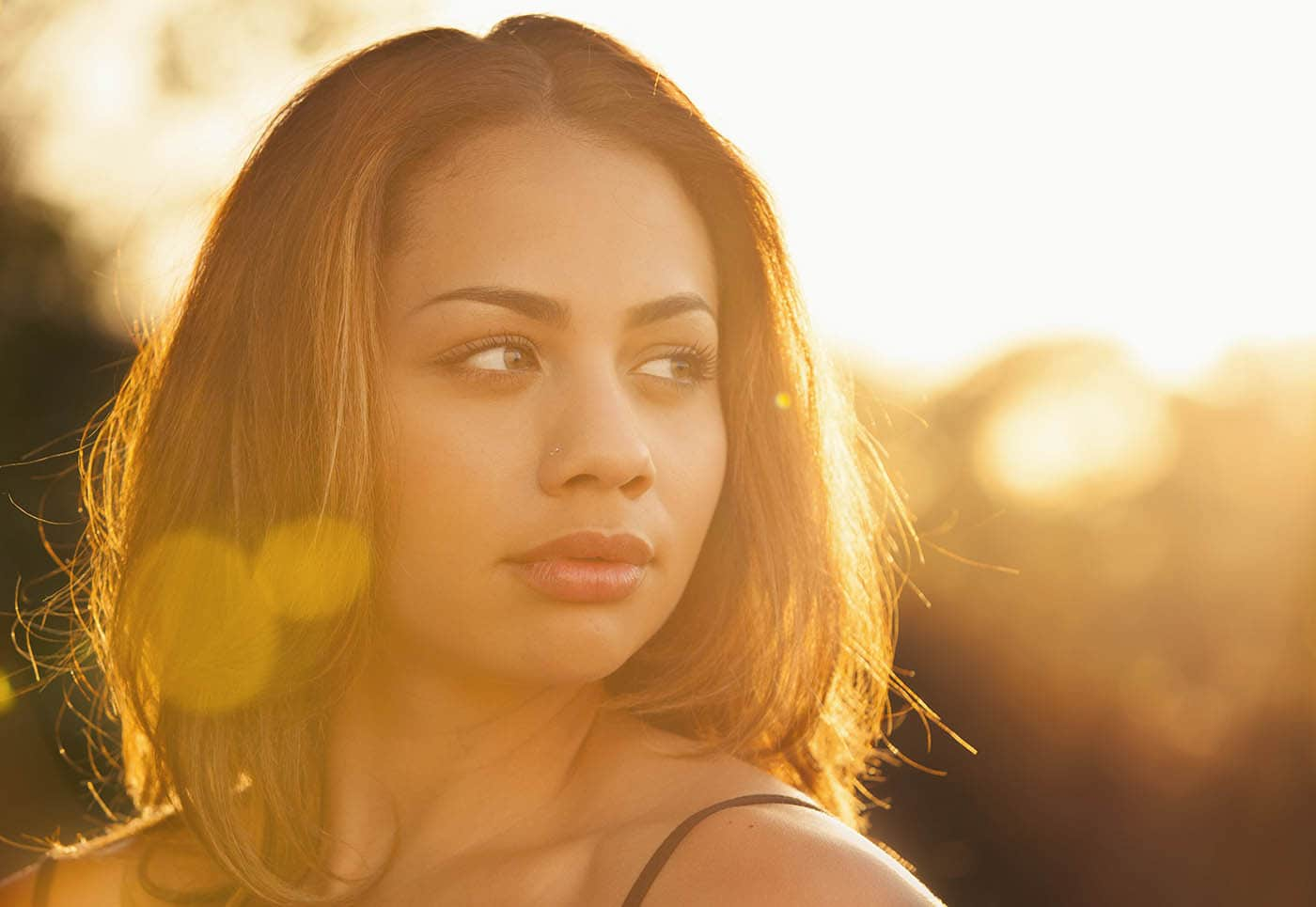 Backlit portrait with lens flare of a young woman staring into the distance on a summer day.