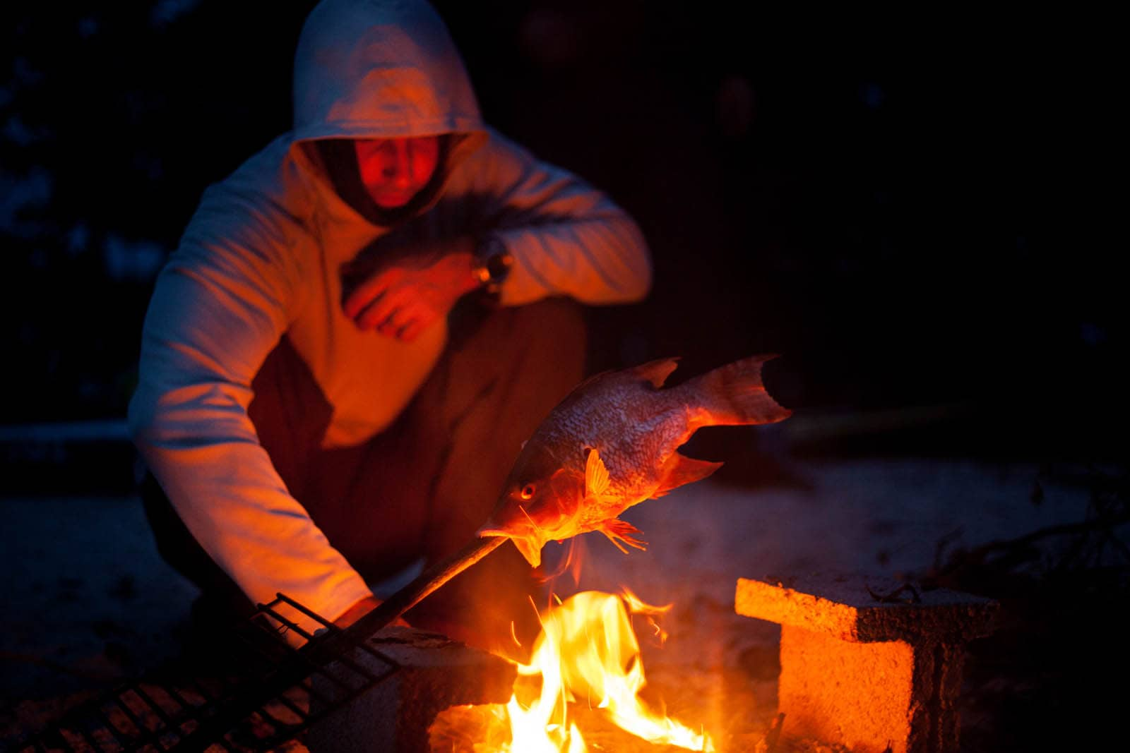 Cooking fish for dinner over an open fire while camping.