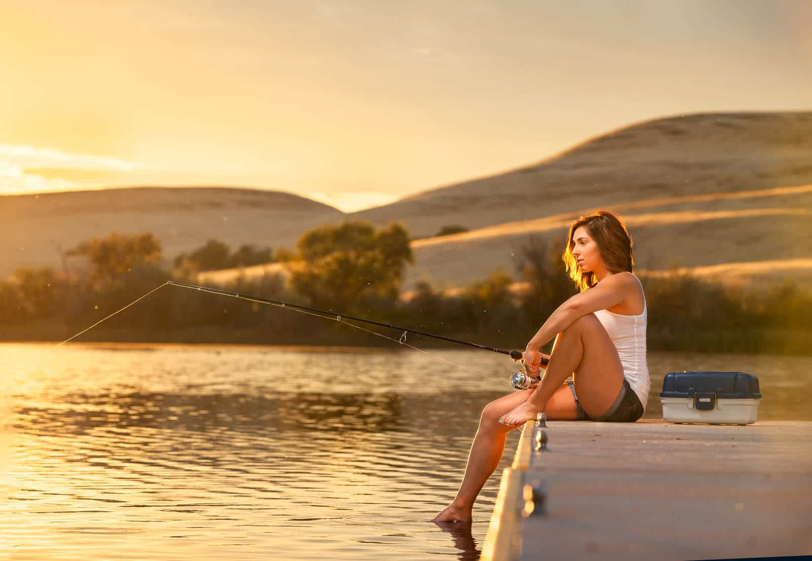 Young woman fishing from a dock on a small lake at sunset.