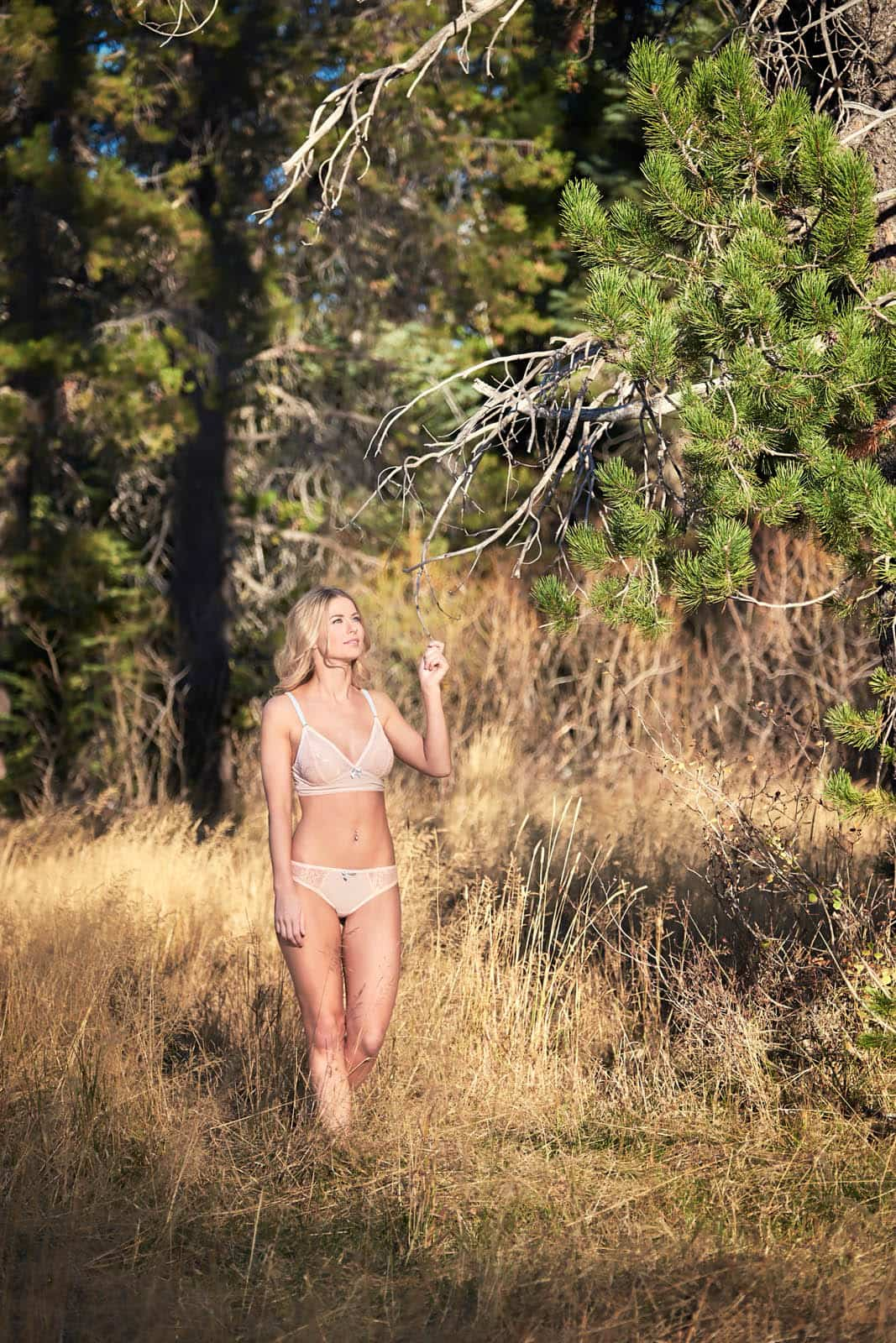 A woman in lingerie walking through a mountain meadow.