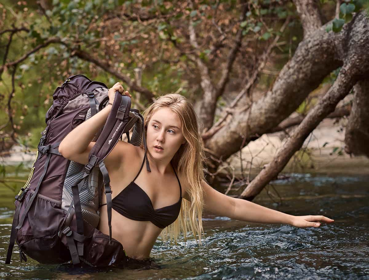 A young woman holding her backpack high when crossing a mountain creek in the Sierra Nevada Mountains of Northern California.