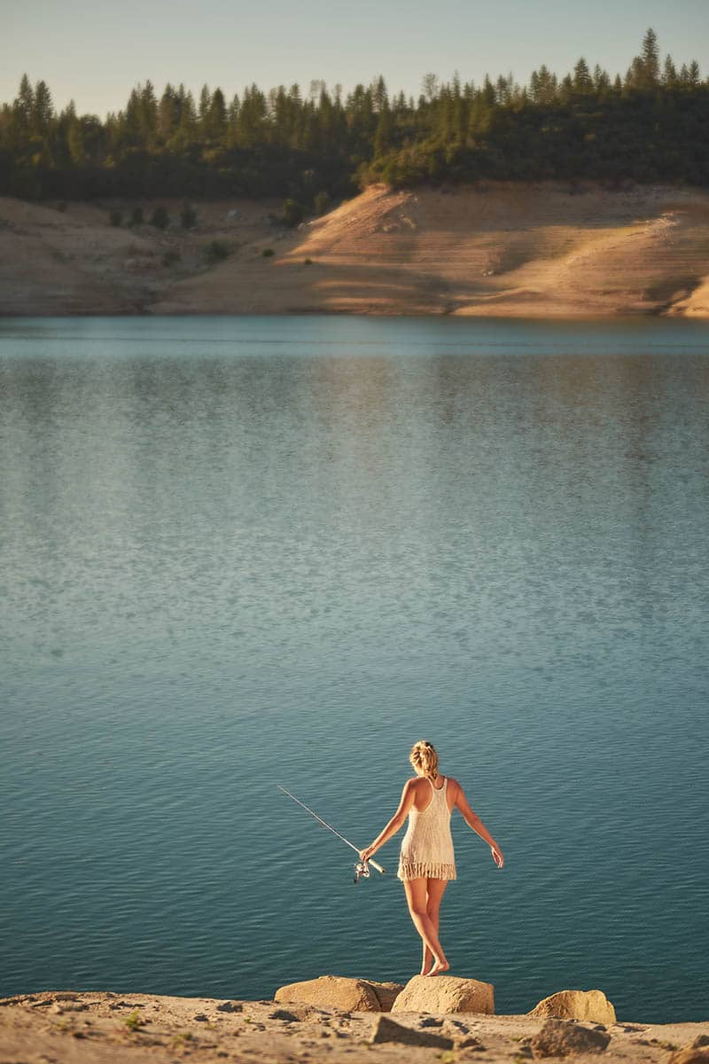 A young, barefoot woman walking to a lake in the late afternoon of a Summer day.