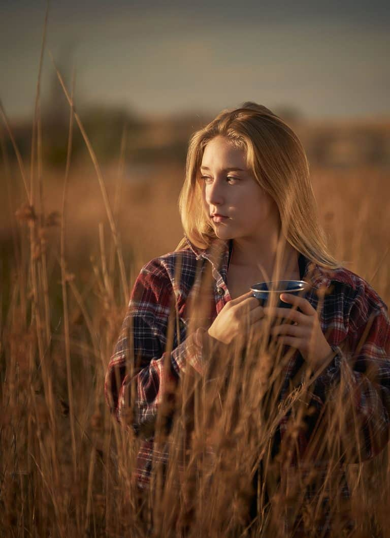 A young woman in a flannel shirt enjoying an early morning cup of coffee.