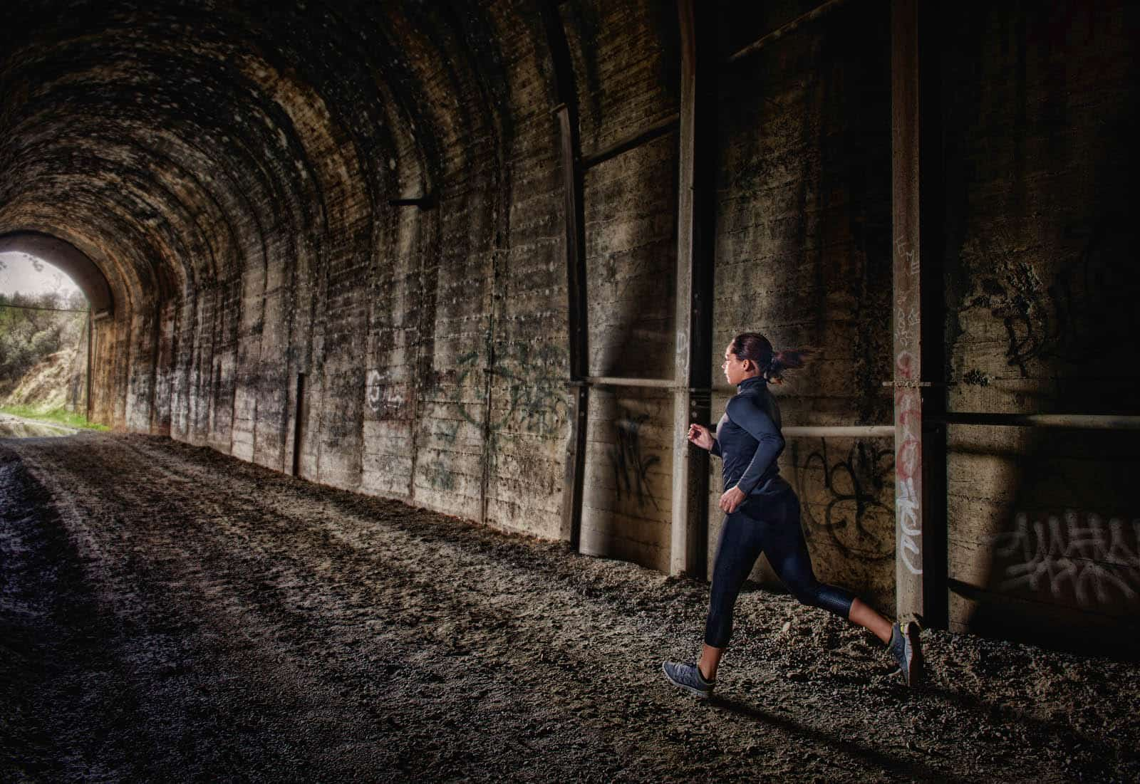 Woman running through a tunnel on a morning jog