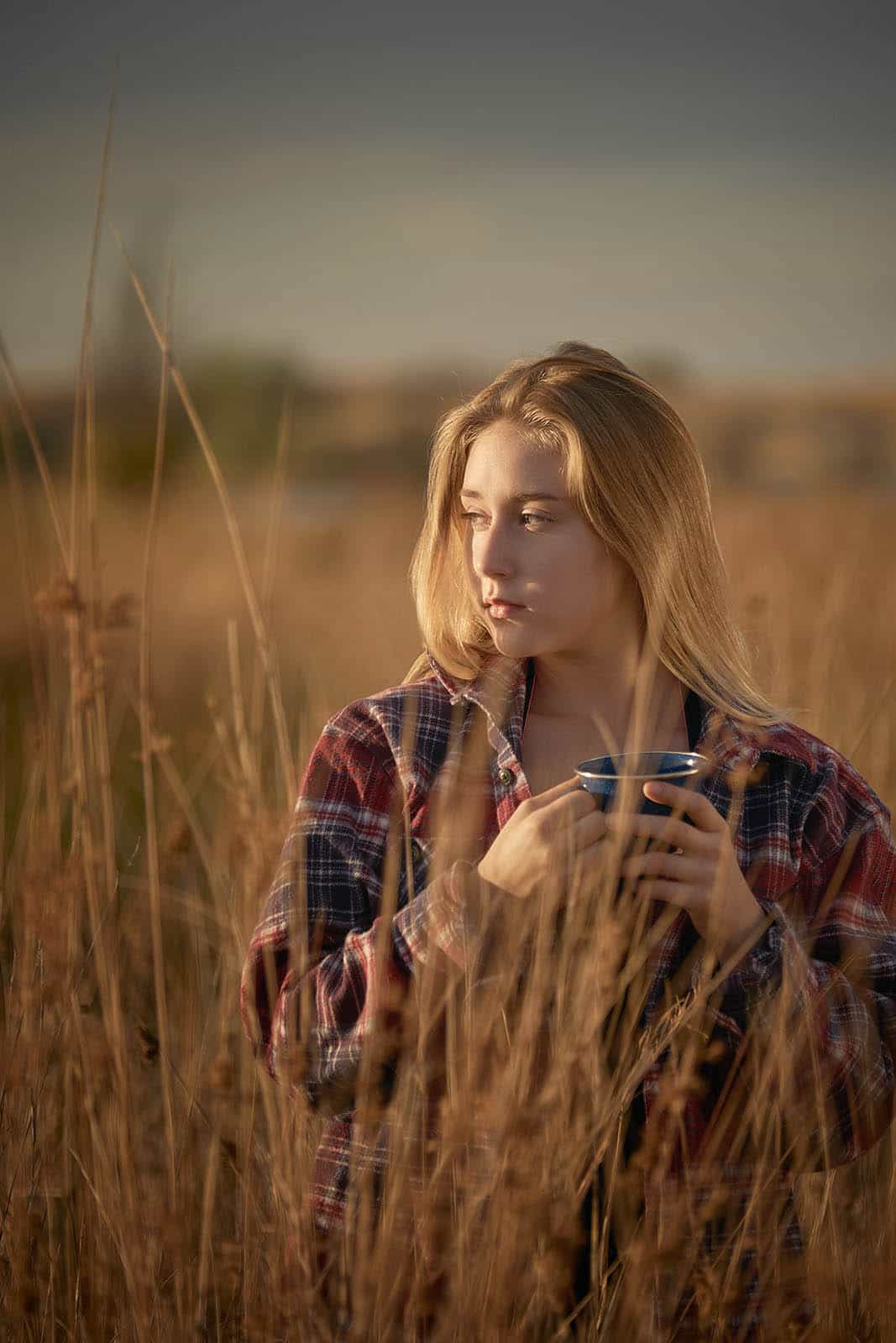 A young woman in a flannel shirt drinking coffee outdoors in a field.