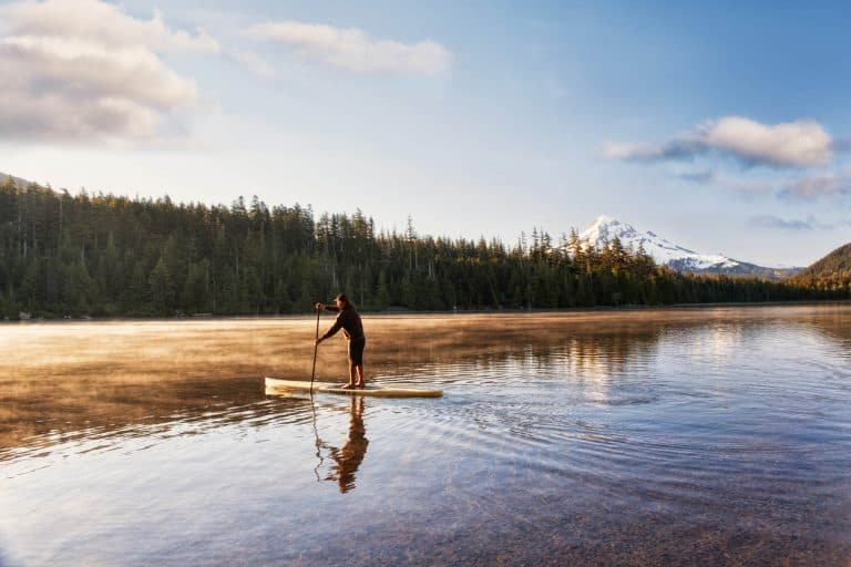 Paddle boarder crossing a mountain lake at sunrise.