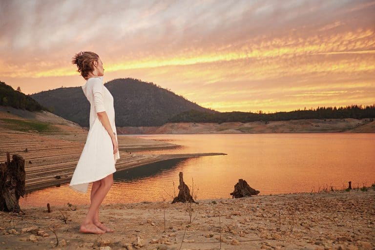 Woman watching the sunset on the shore of a remote mountain lake