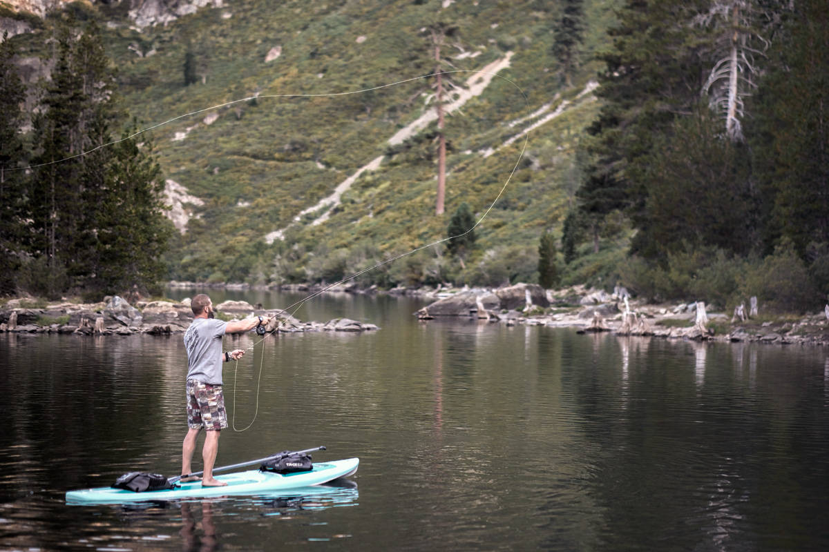 A man casting a fly pole while standing on a paddle board in a mountain lake in Northern California,