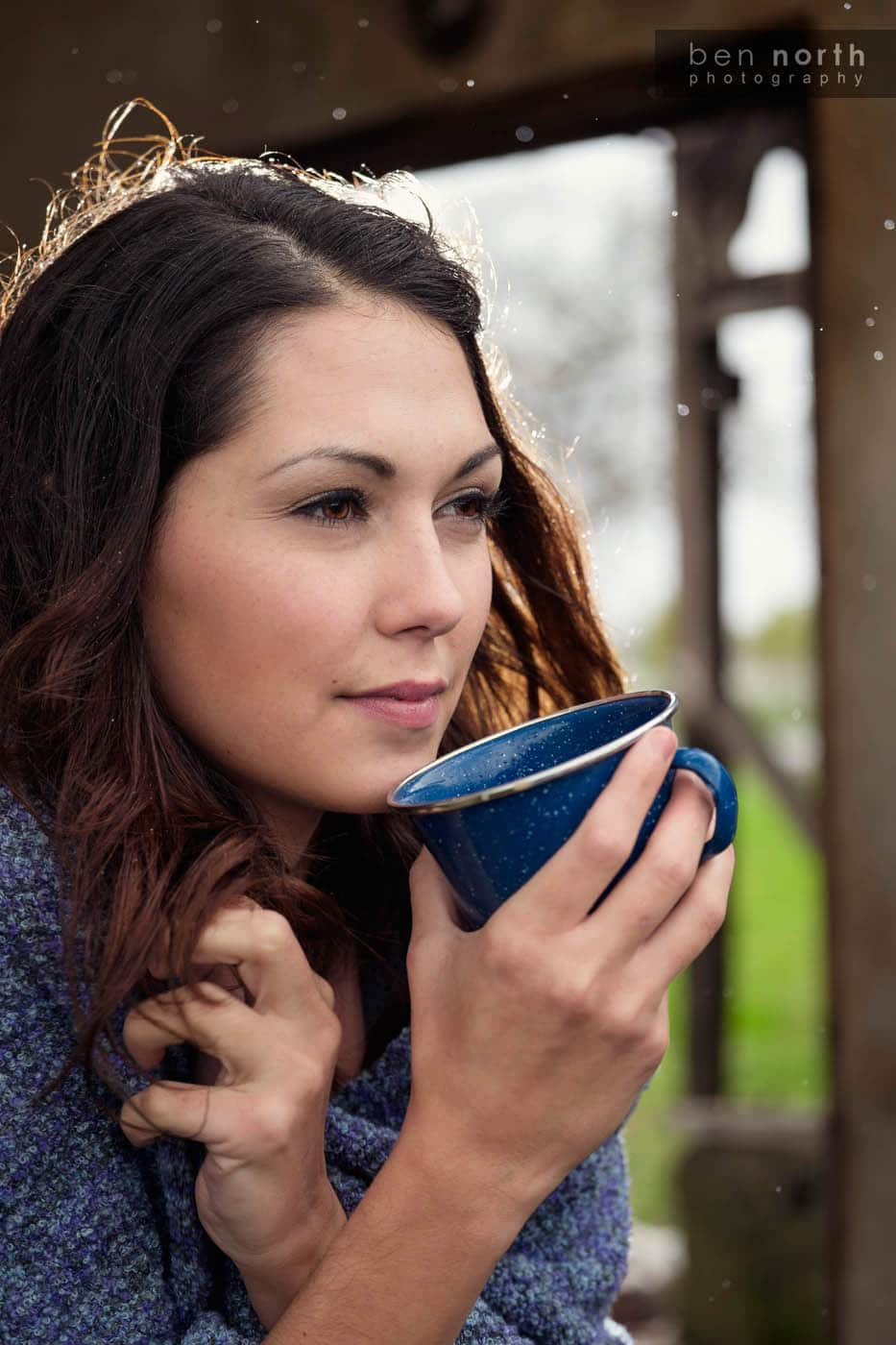 Woman drinking coffee on a farm first thing in the morning.