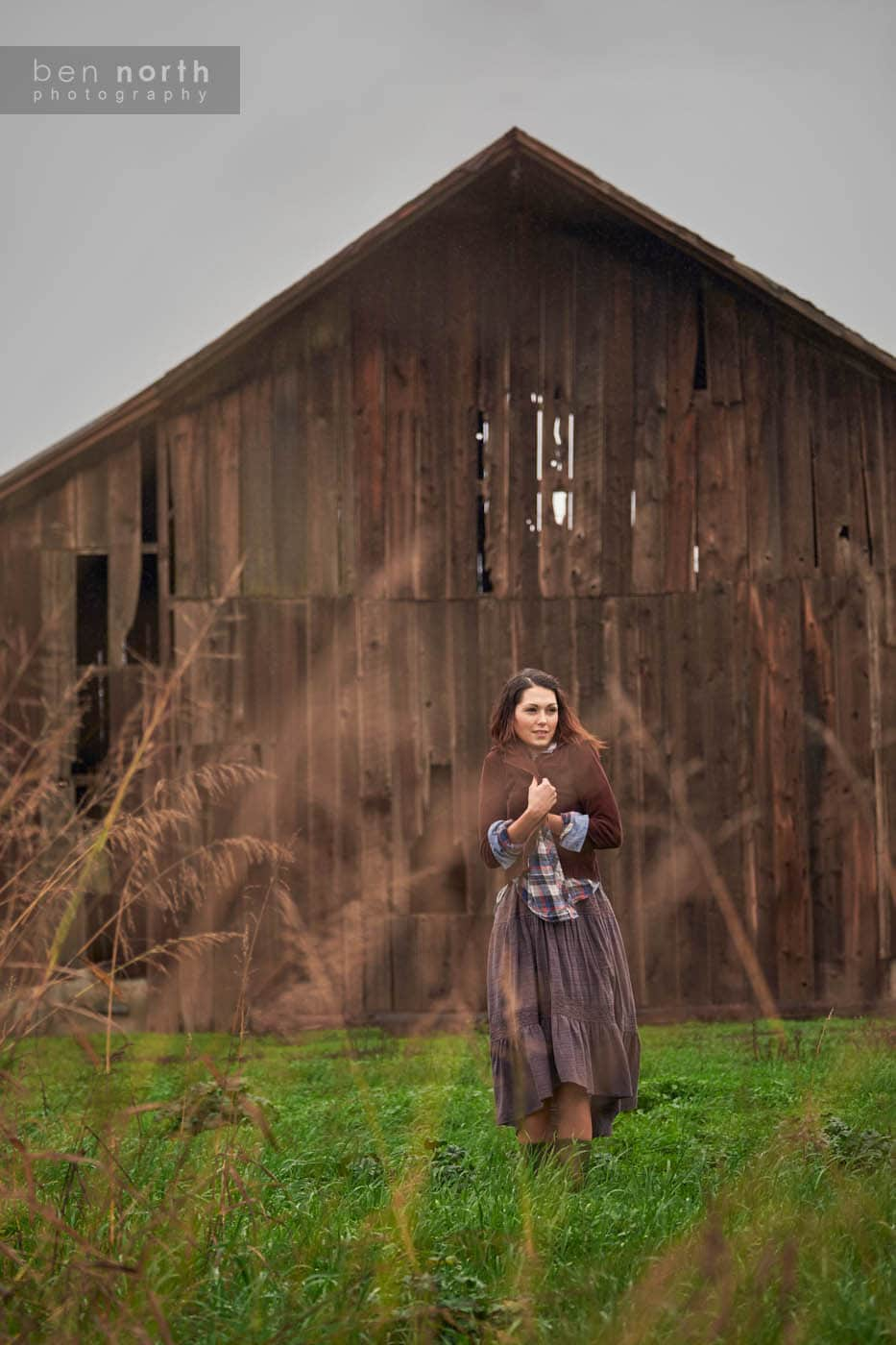 A young woman wearing Free People clothing standing in a field next to a barn on a cold, Winter day.