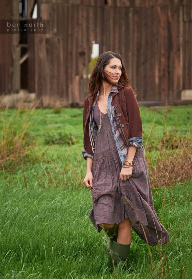 Woman in a dress and rain boots walking through a field on a farm.