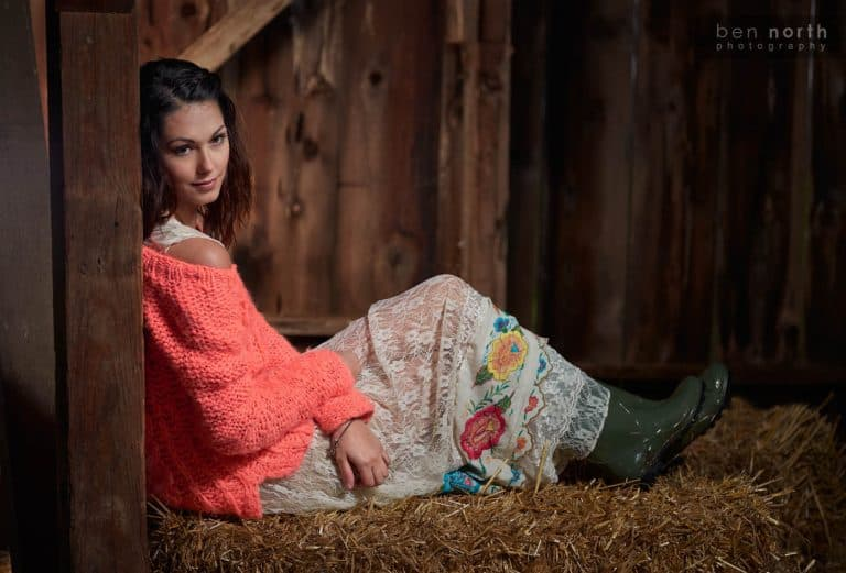 Girl in a dress and rain boots resting in a barn.