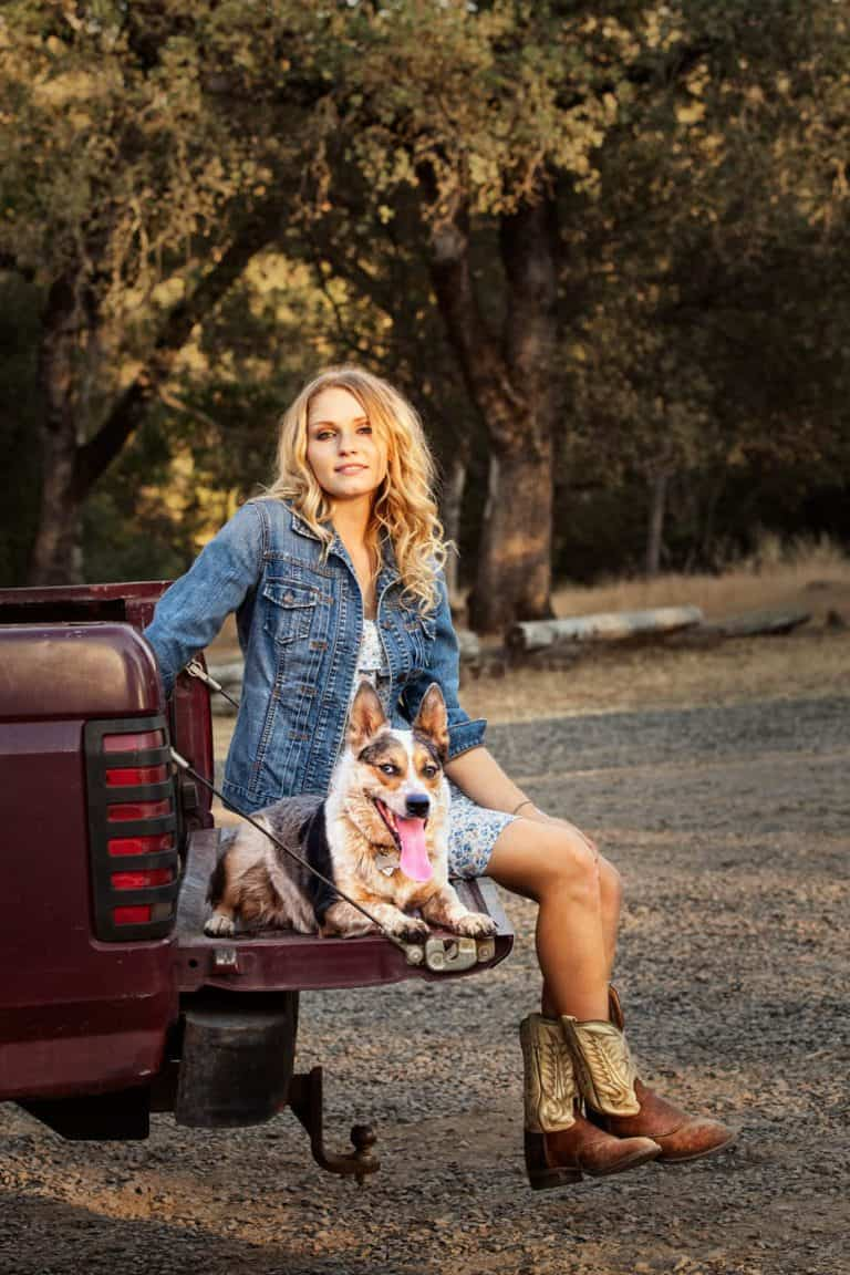 Country girl with her blue heeler herding dog sitting on the tailgate of her truck.