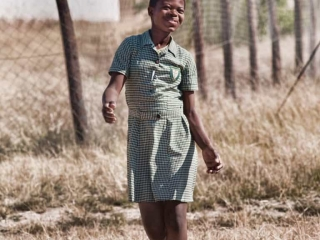Swziland girl walking from school to a soccer game.
