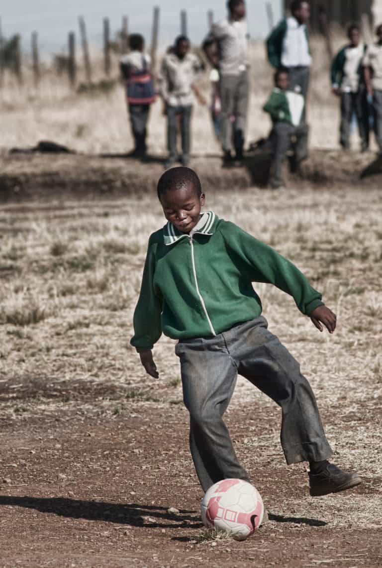 Swaziland boy playing soccer after school in a field.