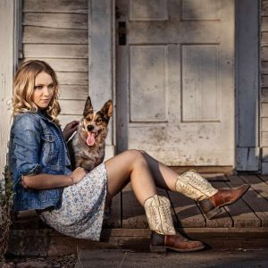 Country Girl in cowboy boots sitting on a front porch with her dog.