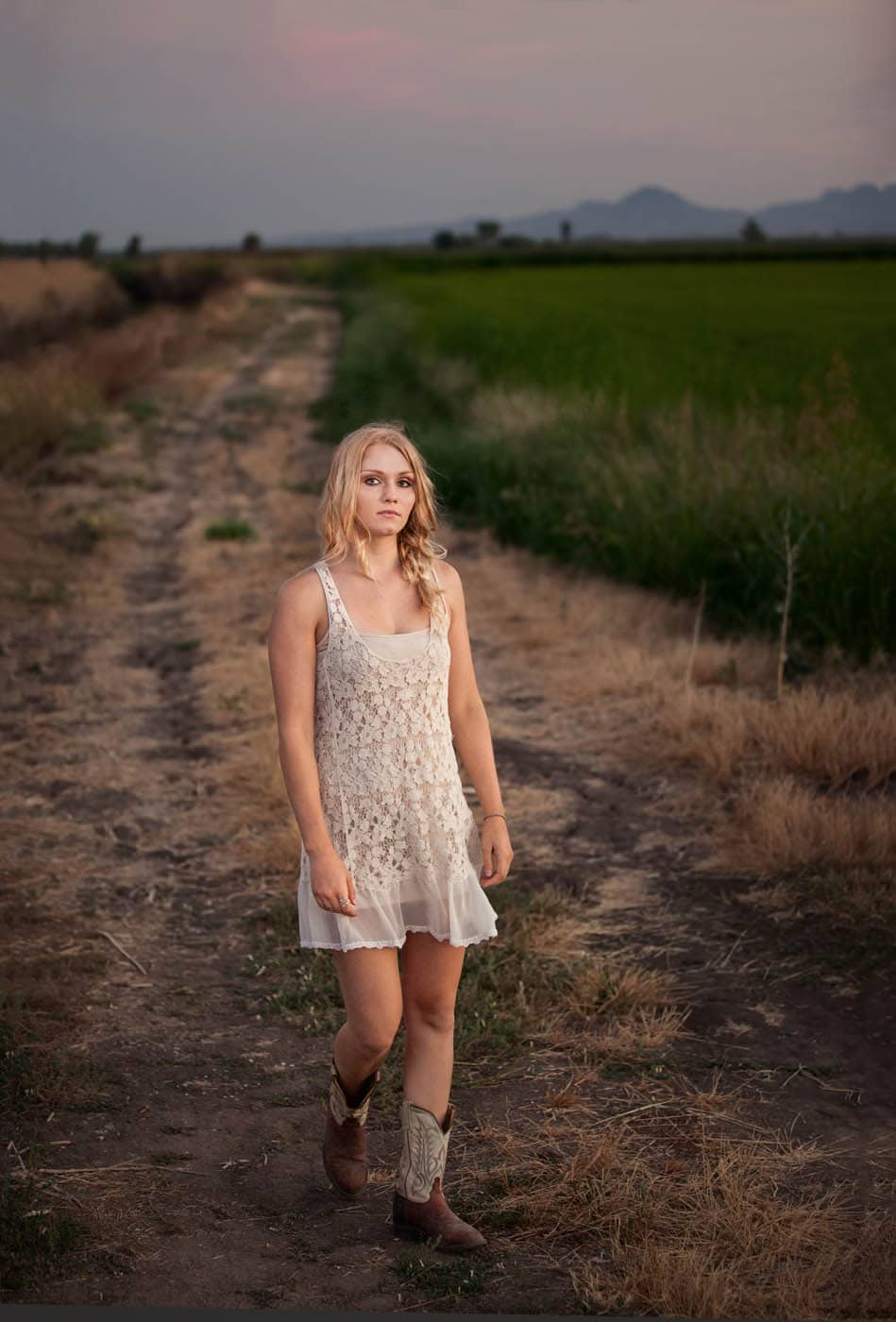 Country girls wearing a Free People Slip and cowboy boots walking through a field on a farm.