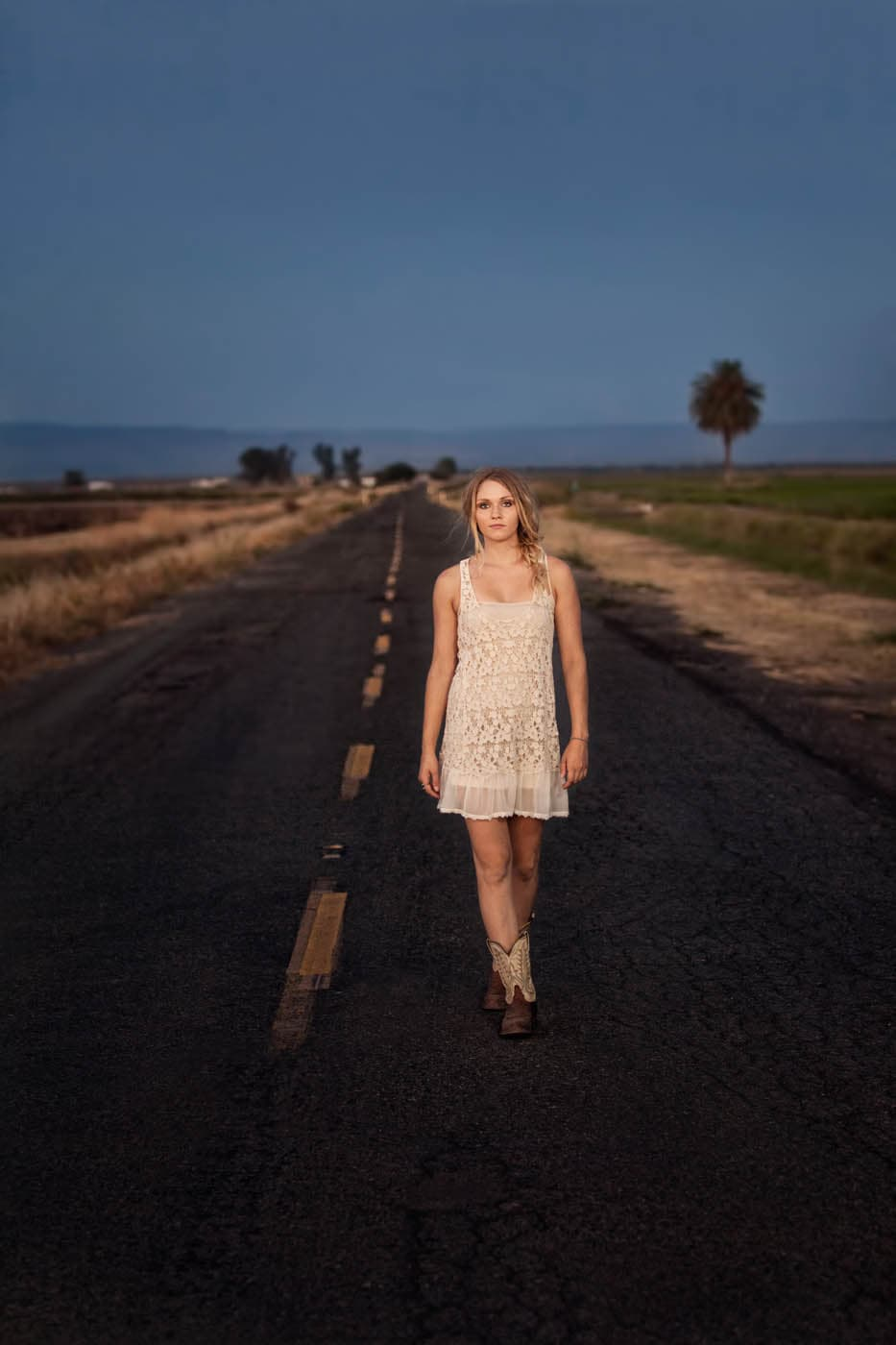Young woman in cowboy boots and a Free People slip walking down a back road in a rural area on a Summer evening.