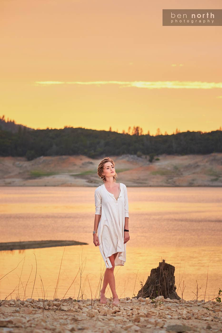 Young woman walking a long the rocky shore of Oroville Lake.
