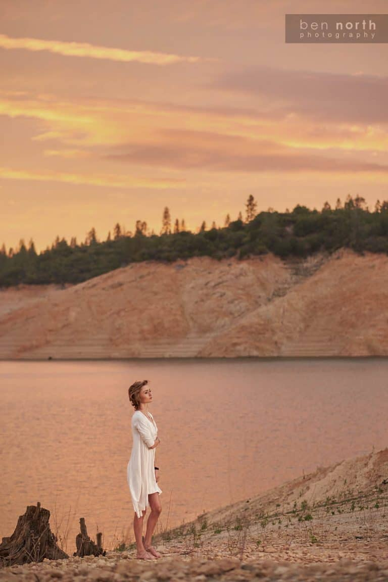 Young woman wearing a Fresh Laundry Tunic walking along the rocky beach of Oroville Lake